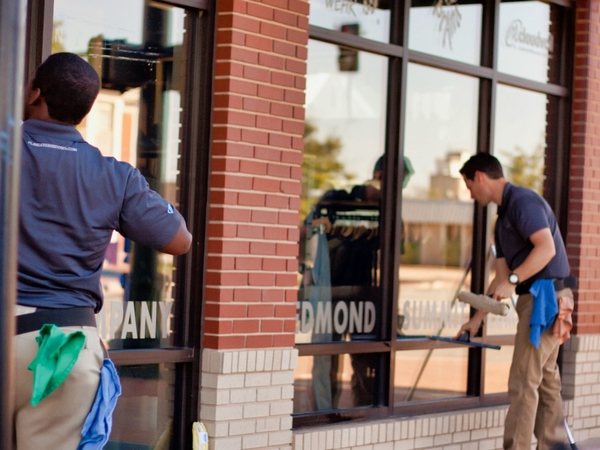 Professional window cleaners in Edmond Oklahoma wash store front windows.