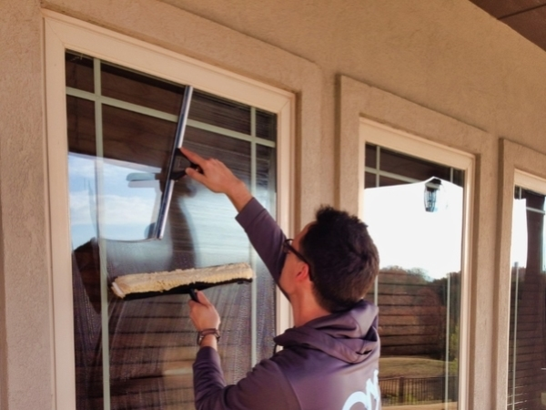 A man holding a window washing brush and squeegee working on washing a home window.