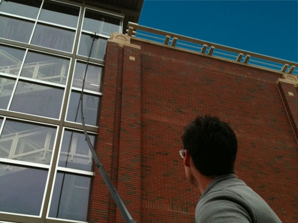 High windows on a commercial business being cleaned from the ground with a long window cleaning pool.
