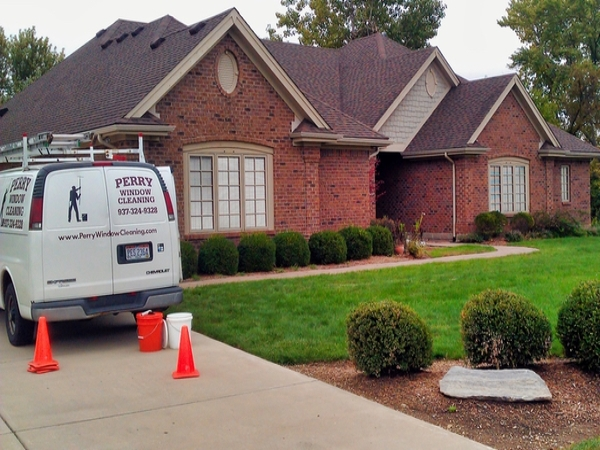 A brick house with Perry Window Cleaning van parked in the driveway ready to have their windows cleaned.