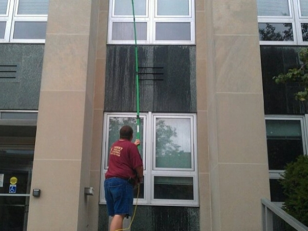 Commercial window cleaning job being done by a team member with a water fed pole.