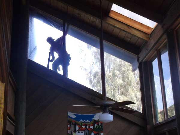 A well trained window cleaner beautifully cleaning a large high window on the exterior of a home in Hawaii.