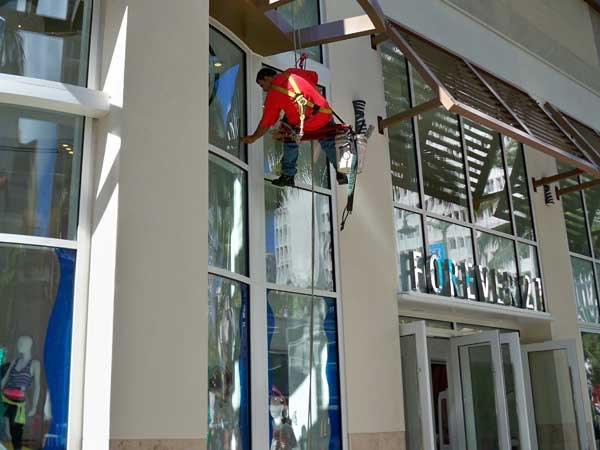 Window cleaner hanging on a rope cleans hard to reach windows at a local business.