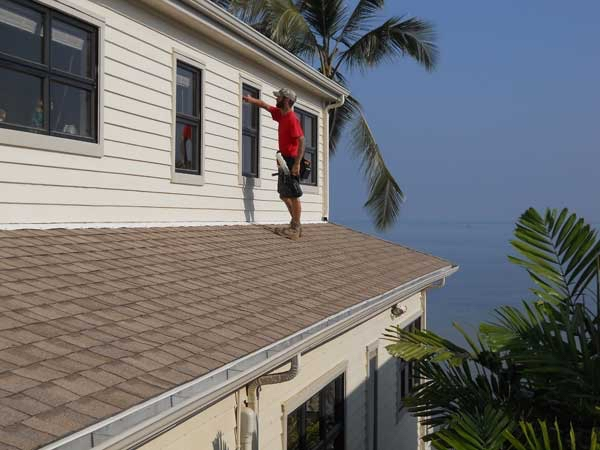 A house facing the ocean is getting windows cleaned by Quality Window Cleaning in Hawaii.