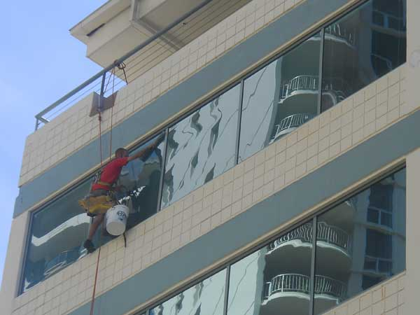 Window cleaner hanging by rope cleaning a window on a high-rise in Pearl City.