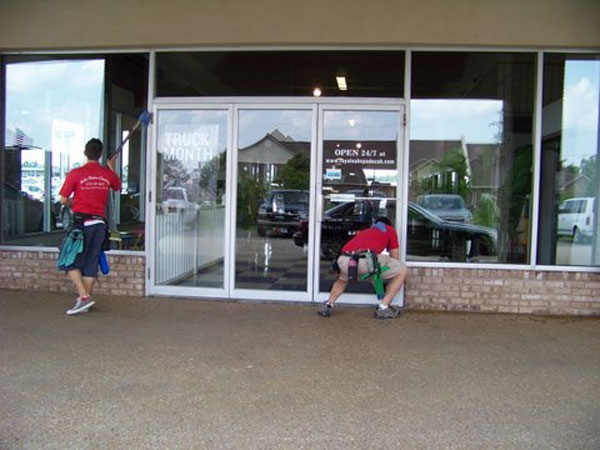 Professional friendly window cleaners wash windows of a store front in Paducah Kentucky.