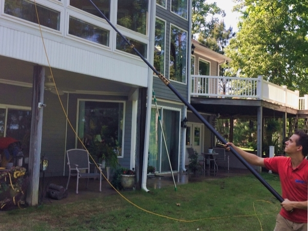 A team member cleans a large two story home with a water fed pole.