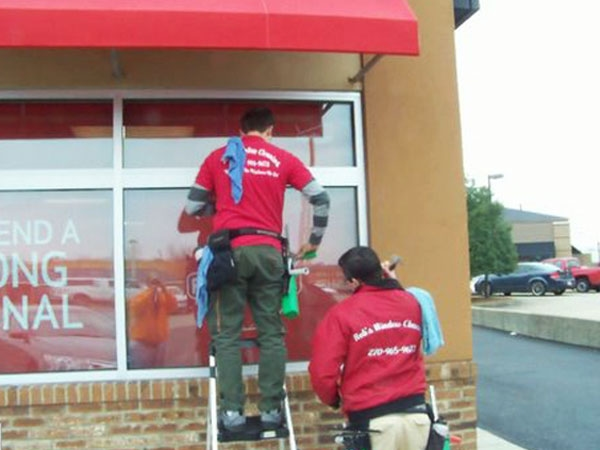 Window Cleaners service a local business by cleaning store front windows.