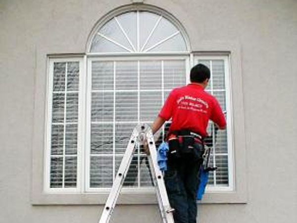 Professional window cleaner is cleaning the window of a home in Murray Kentucky.
