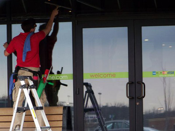 A window cleaner standing on a ladder cleans store front windows in Murray Kentucky.