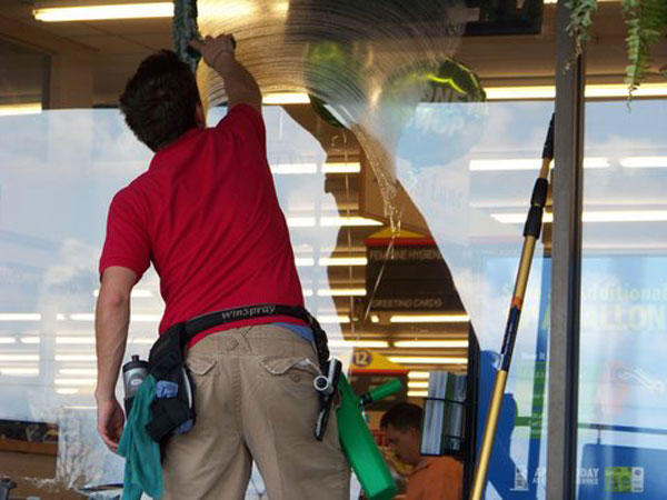 A professional window cleaner squeegees commercial windows to be streak free in Paducah.