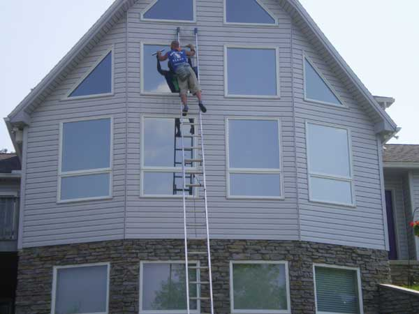 Home with very high windows having its windows cleaned by a highly skilled window cleaner in Baltimore Maryland.
