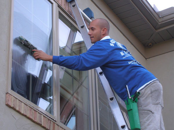 Professional friendly staff member from Squeegee Klean washes window of home in Baltimore Maryland.