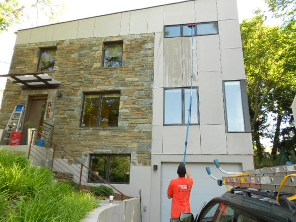 Large flat roof home having exterior windows cleaned on the second story with a water fed pole.
