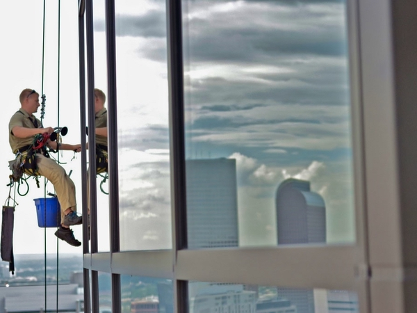 Highly trained window cleaner washing high rise windows in the air in Denver Colorado.
