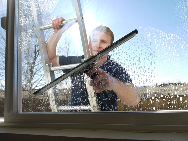 Friendly Super Clean window washer takes soapy water off window with squeegee in Denver Colorado.