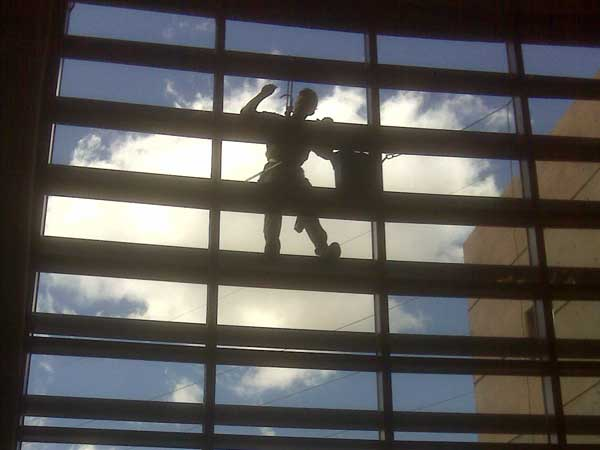Well trained window cleaner in Santa Fe New Mexico washing windows for commercial property.