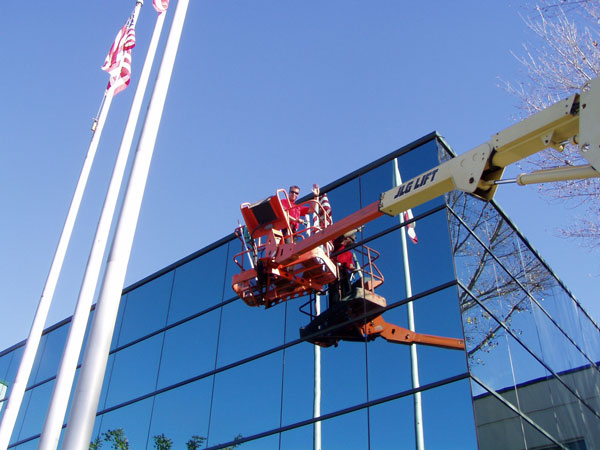 High rise windows being cleaned by window washers on a lift in El Cajon California.