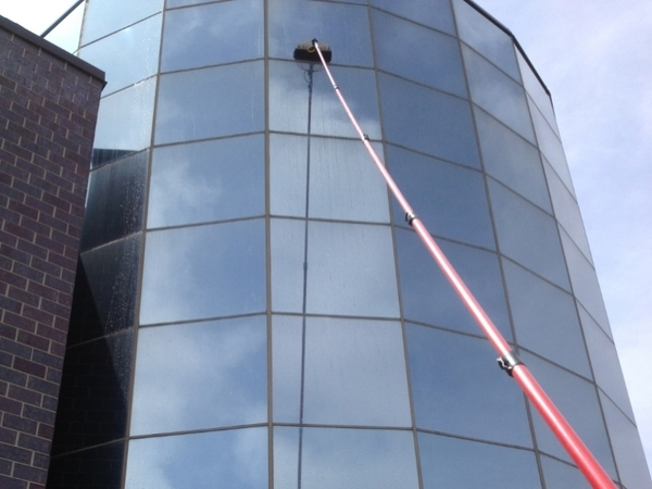 Windows on the exterior of a business being cleaned by professionals.
