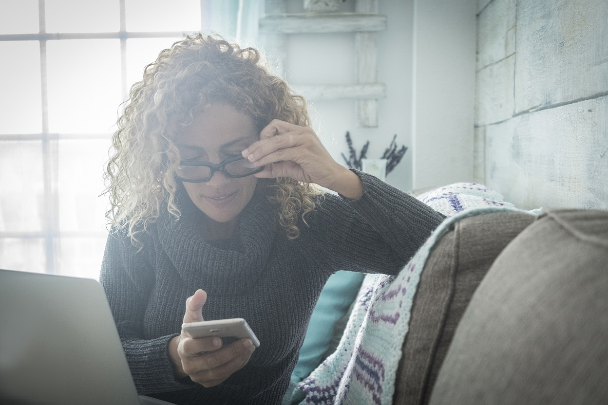 curly-haired woman in eyeglasses sitting on a couch looking down on her phone