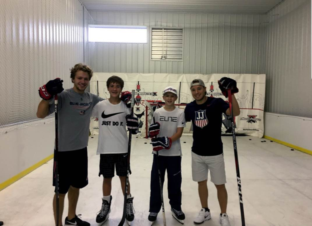 Cam Atkinson and coaches showing youth hockey players skills