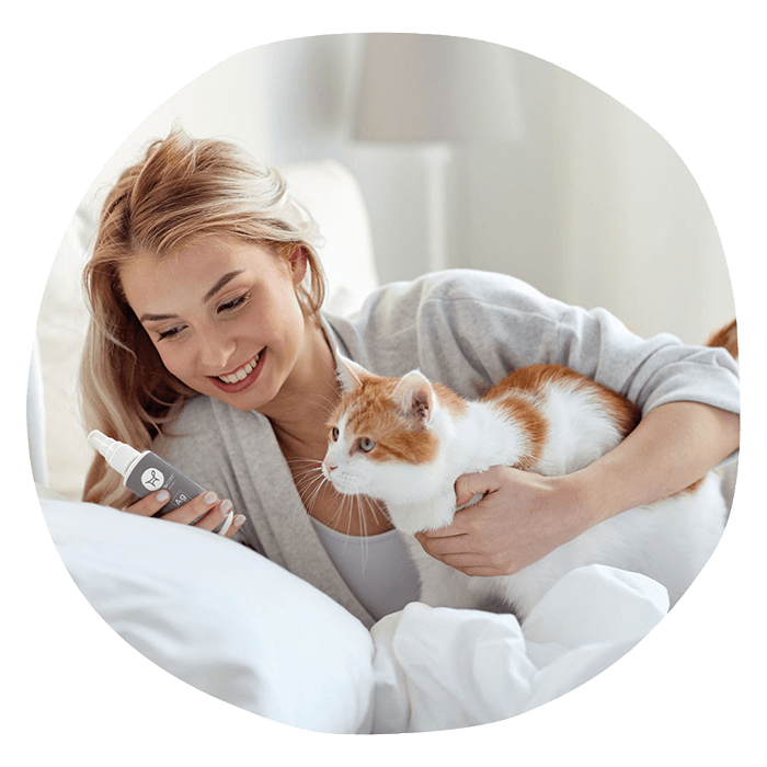 Woman smiling with cat and silver spray Fauna Care
