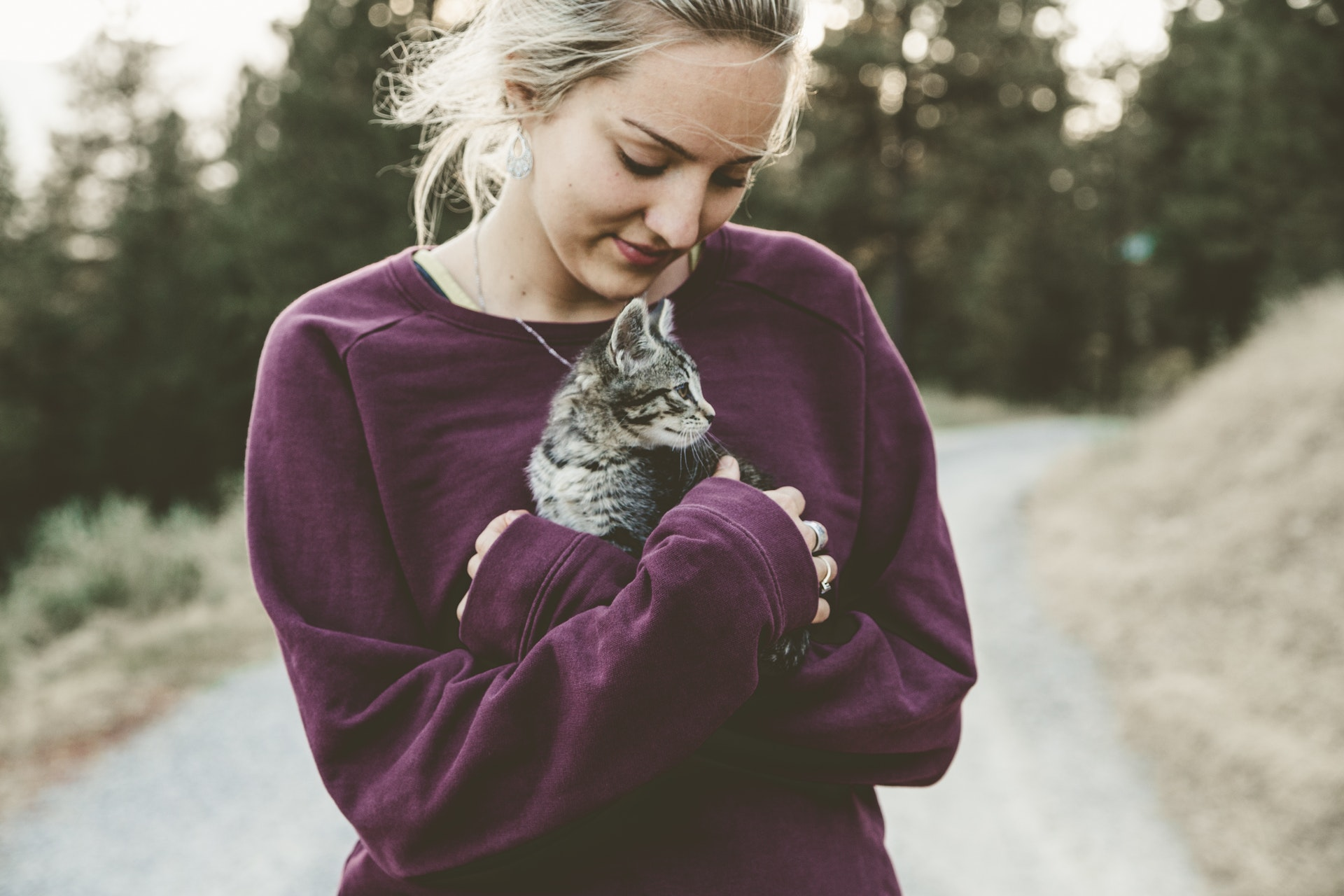 girl walking outside with kitten in arms