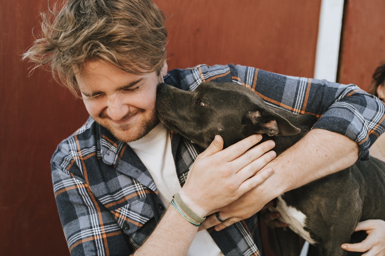 a man in a plaid shirt holding his dog