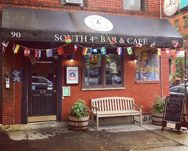 The storefront of South 4th Bar & Cafe, with flags hanging from the awning