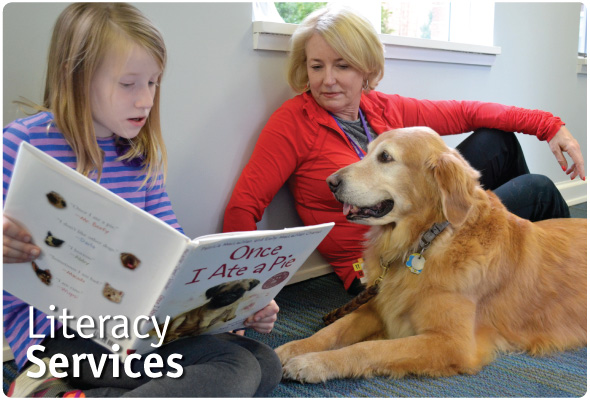 A girl with blonde hair reads a picture book to a happy golden retriever while the dog's owner looks on