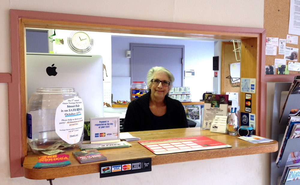 The front desk of Sunset Veterinary Hospital, staffed by a smiling woman