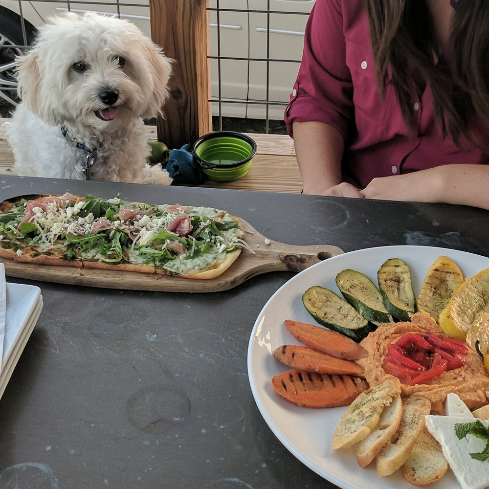 a woman and her dog enjoying their food