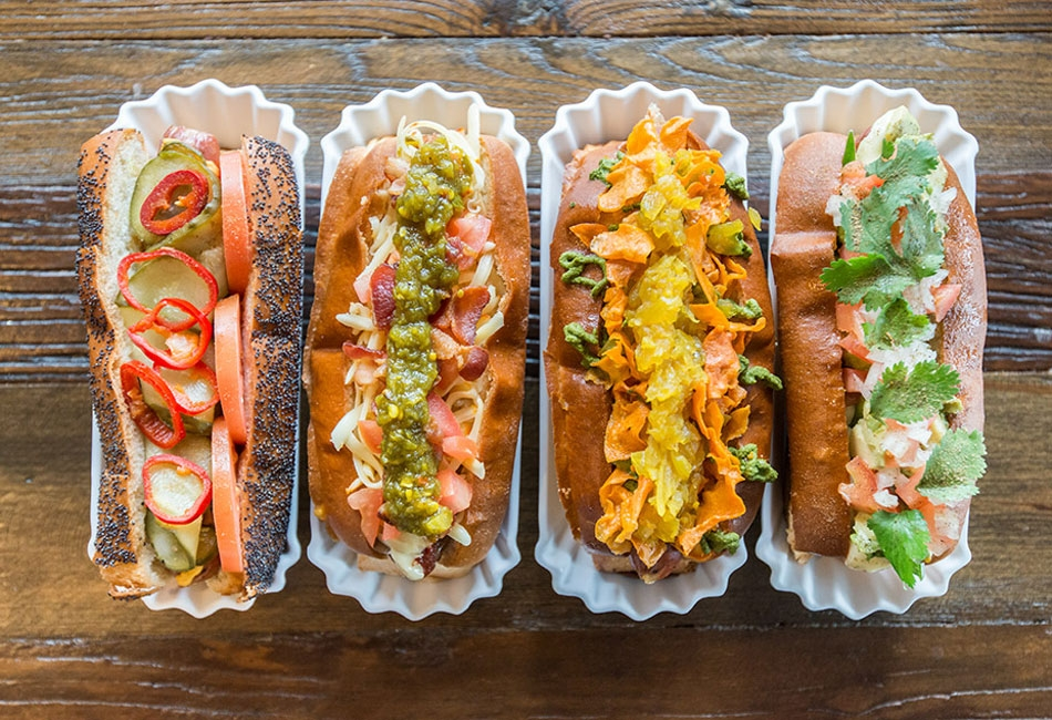 four hot dogs loaded with toppings
