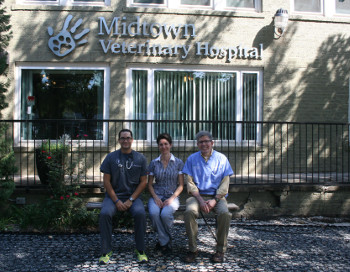 Three vets sit outside Midtown Veterinary Hospital