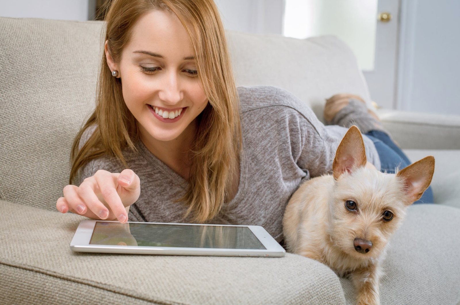A woman with blonde hair lies on a couch with her dog, using a white tablet to play audiobooks.