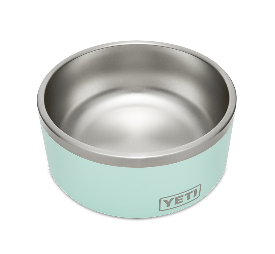 a product image of a YETI dog bowl, which is silver on the inside and pale blue on the outside, and features yeti's text logo inscribed in a rectangle with rounded edges