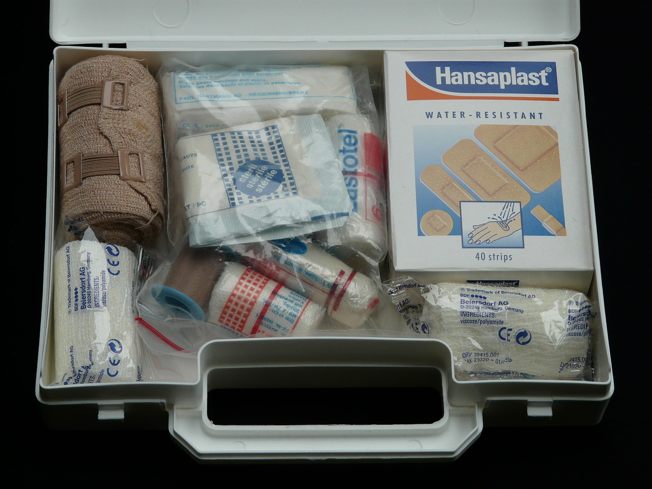 An open safety kit filled with several types of bandages