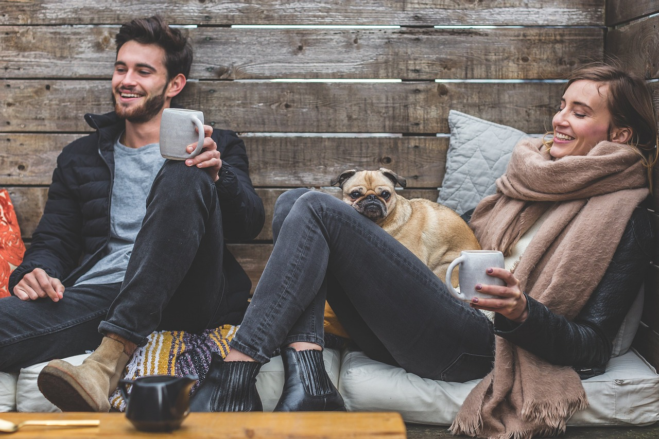 Group of people in a cabin with mugs. A small dog sits in the lap of the woman.