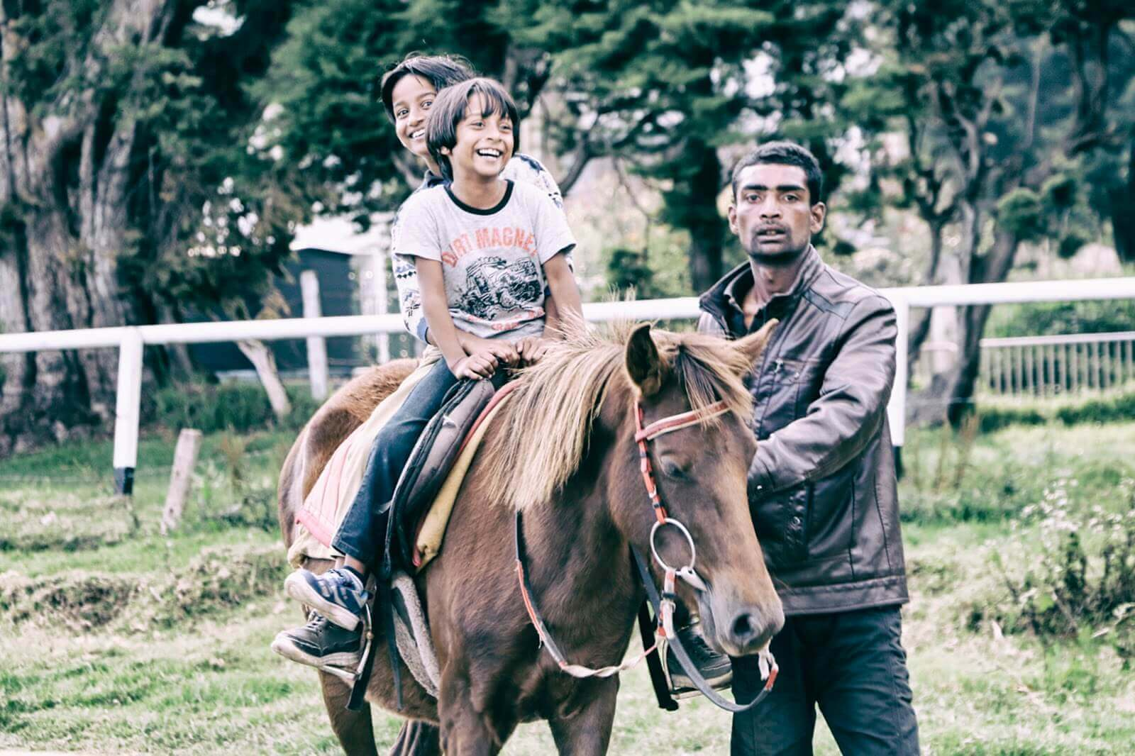 little boys riding horse with parent by side
