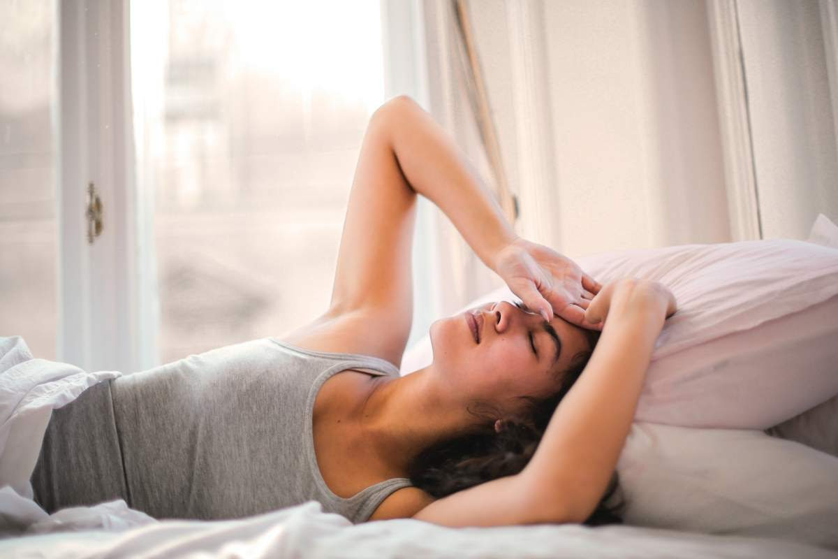 Woman lying in bed with her hand to her forehead looking like she can't get to sleep