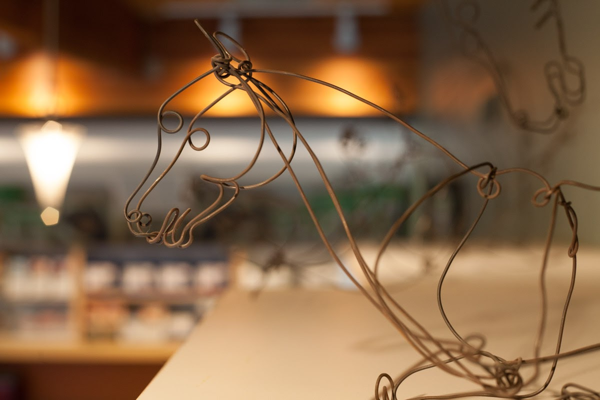 Wire sculpture of a horse with blurred background of a veterinary hospital waiting room