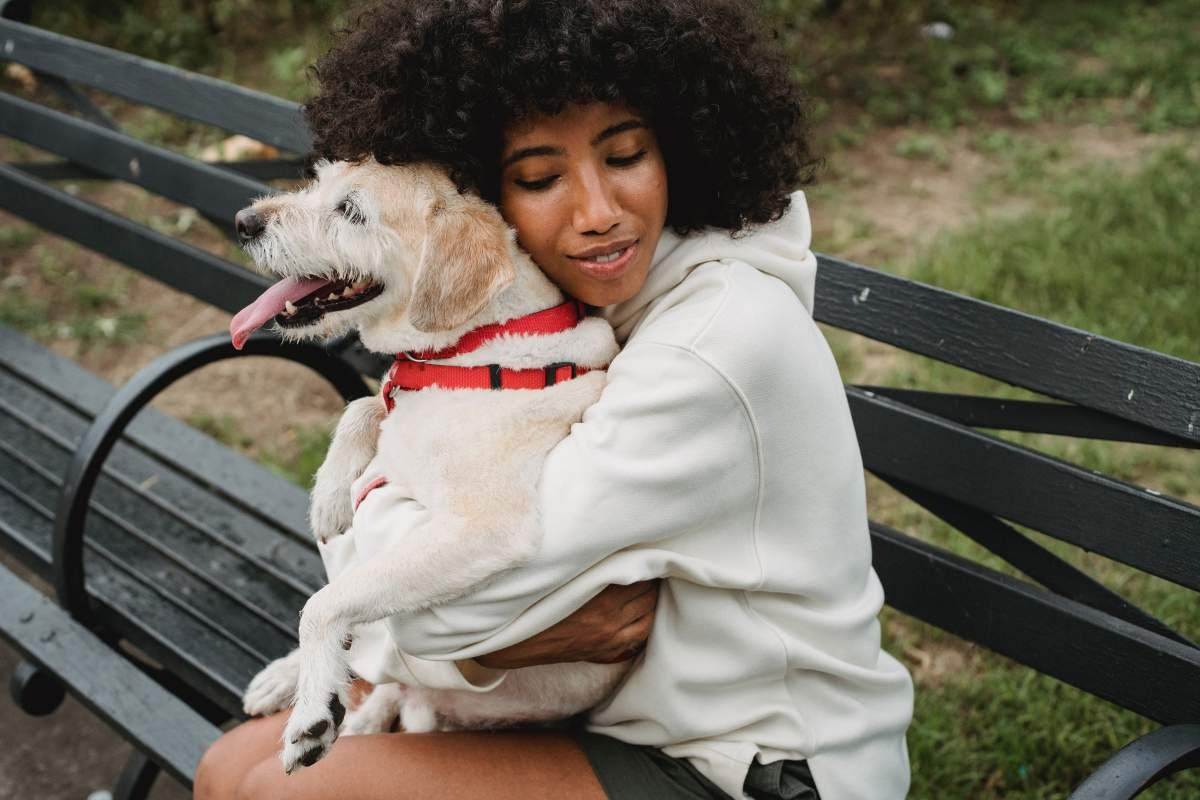 Woman sitting on a park bench hugging her dog who's sitting on er lap.