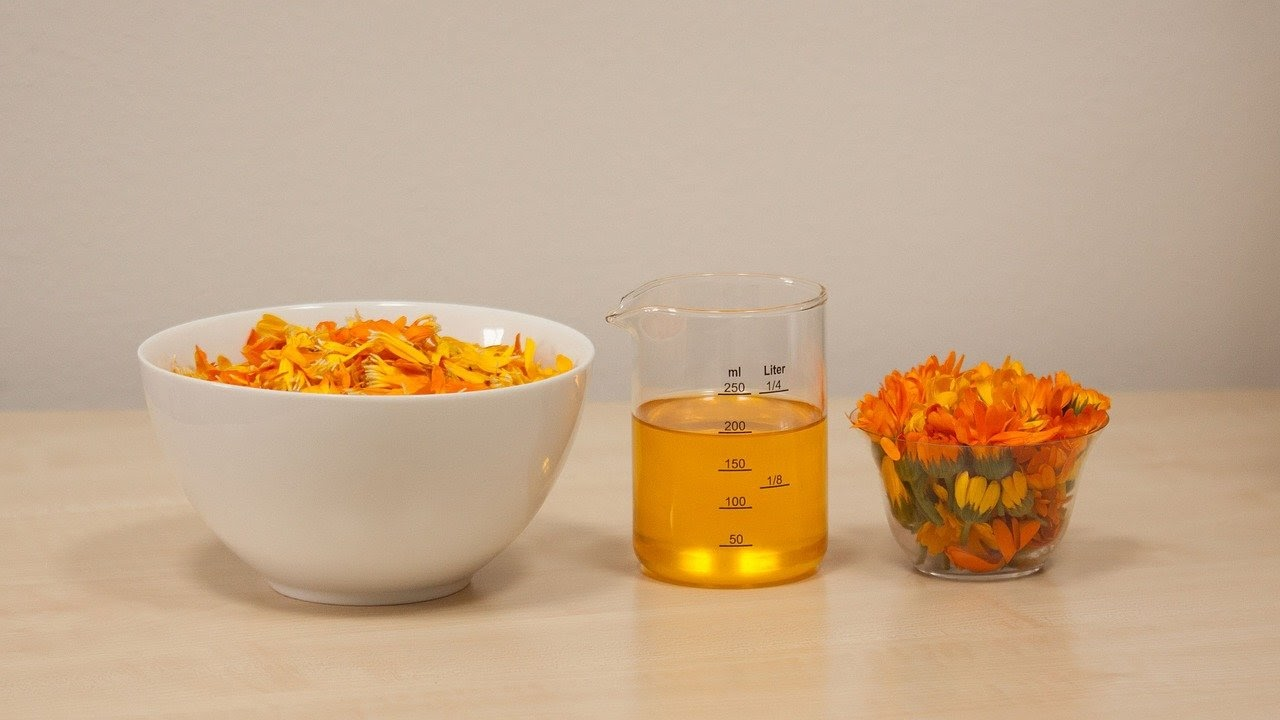A cup of calendula flowers and oil
