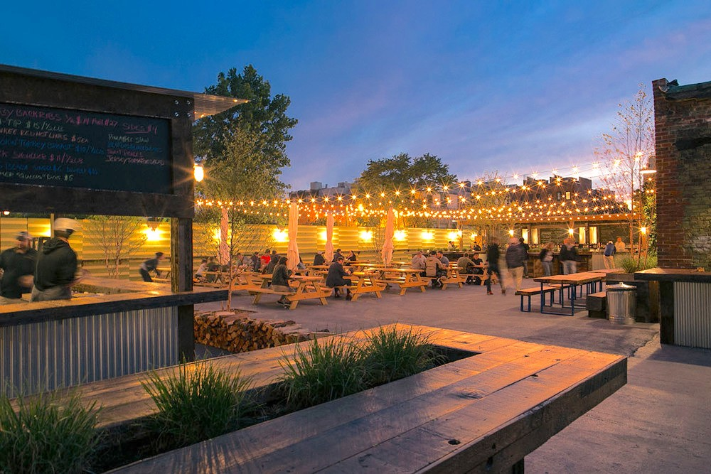 Pig Beach's outdoor seating area with picnic tables and lights