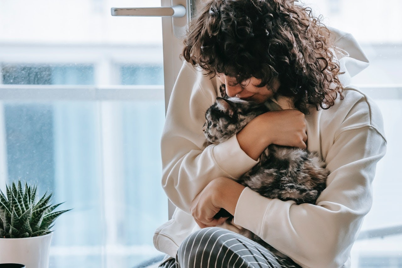 A woman with curly hair hugs her calico cat to her chest in front of a window.
