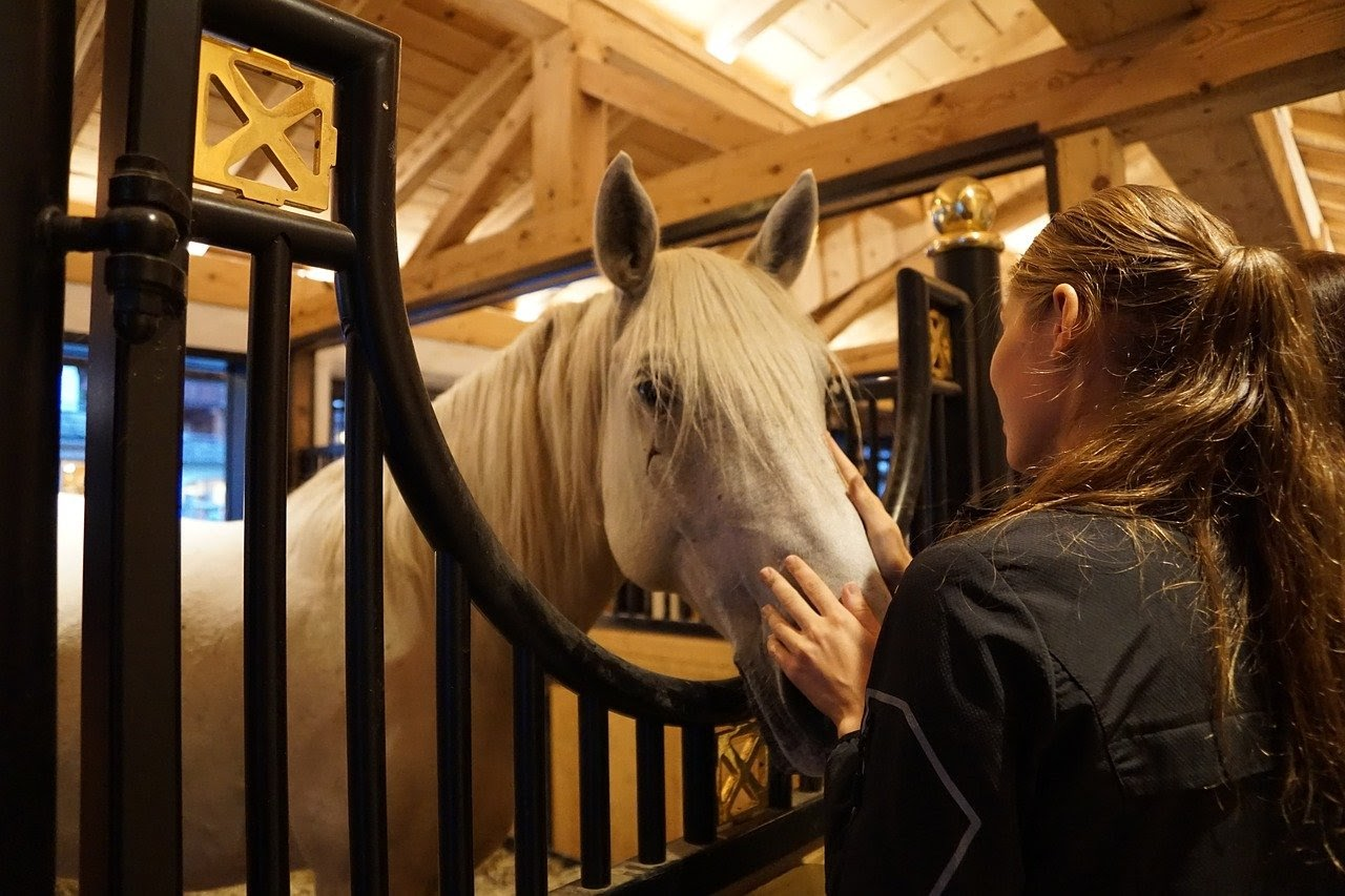 A woman pet's her horse's nose in its stall.