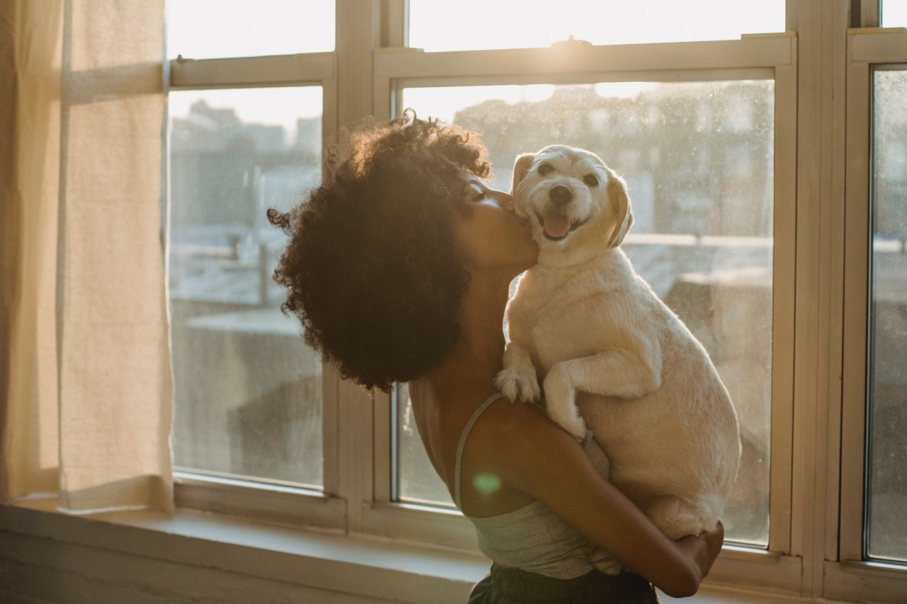 A black woman with natural hair stands by a set of large windows. In her arms she holds a small white dog with a smile on its face. She is giving it a kiss on it's neck.