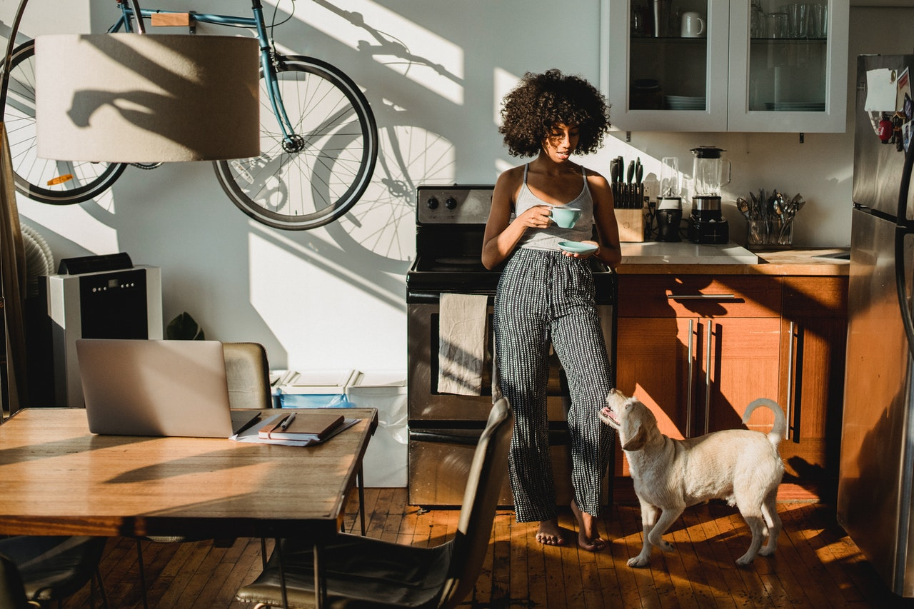 A black woman stands in her kitchen holding a cup of coffee. She is lit by natural light streaming in from the windows. At her feet is a scruffy, white, medium sized dog looking up at her.