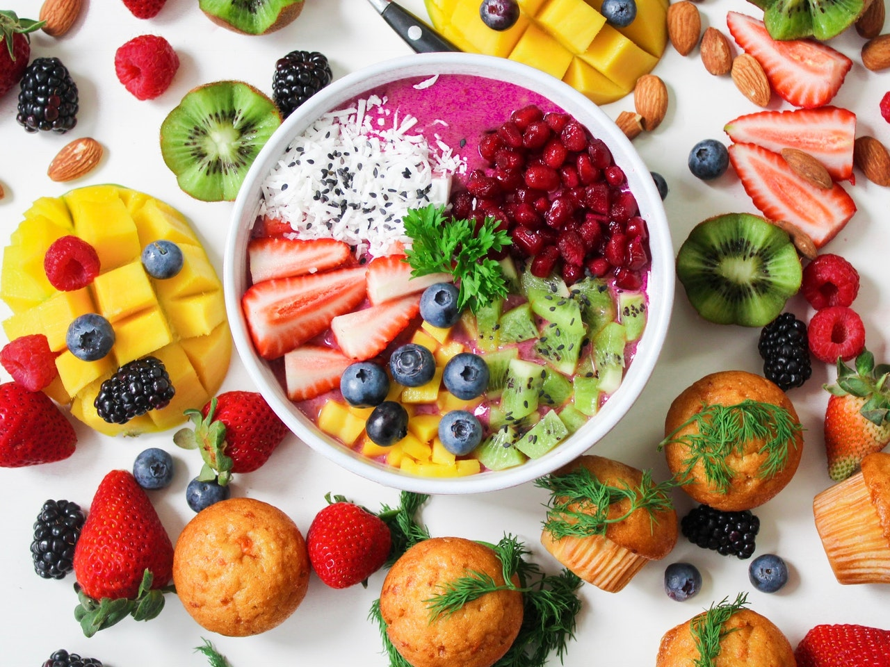 An overhead view of a bowl full of colorful fruit such as strawberries, dragon fruit, pomegranate seeds, kiwi, blueberries, and mango. These same fruits, along with more food like muffins and almonds, surround the bowl.