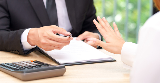 man offering pen to sign contract
